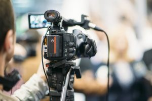 Television camera recording publicity event. Camera in focus, operator and event blurred